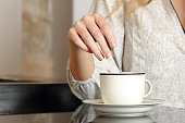 Woman hand preparing a cup of coffee at home