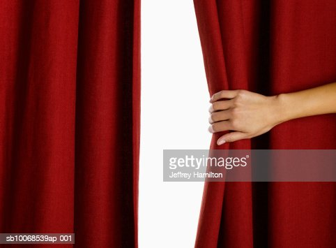 Woman hand pulling curtain, close-up : Stock Photo