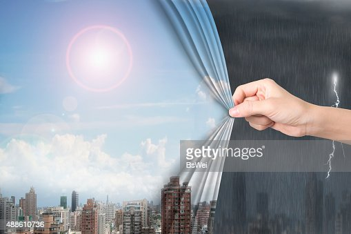 Woman hand pulling sunny sky cityscapes curtain covering stormy : Stock Photo