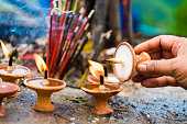 Woman hand with terra-cota oil lamps as religious offerings at temple in Nepal. Incence sticks over blurred background.