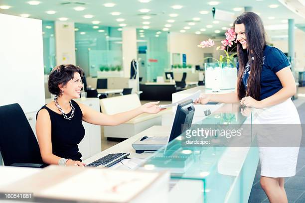 A woman handing a paper to another woman at a desk