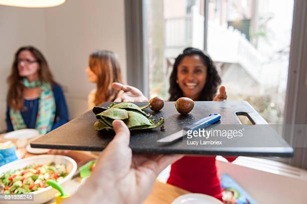 Woman handing avocado peels to the viewer