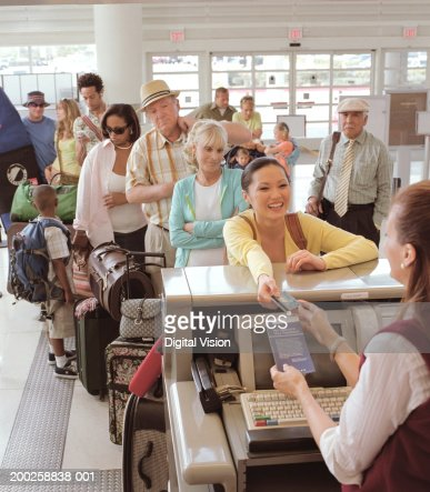 Woman handing bank card to woman at airport check in desk, smiling