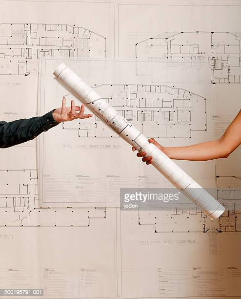 Woman handing blueprints to man, close-up of arms