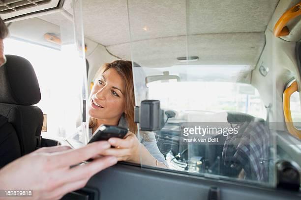 Woman 処理携帯電話のタクシードライバー
