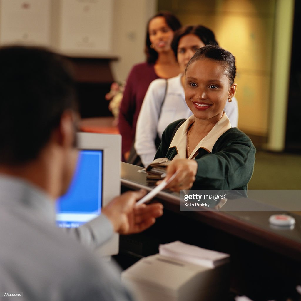 Woman handing check to teller (focus on woman)