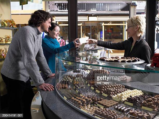Woman handing couple box across counter in chocolate shop, smiling
