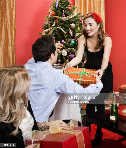 Woman handing gift to man at Christmas party