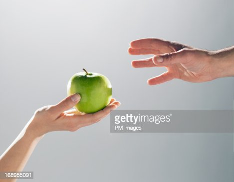 Woman handing man an apple