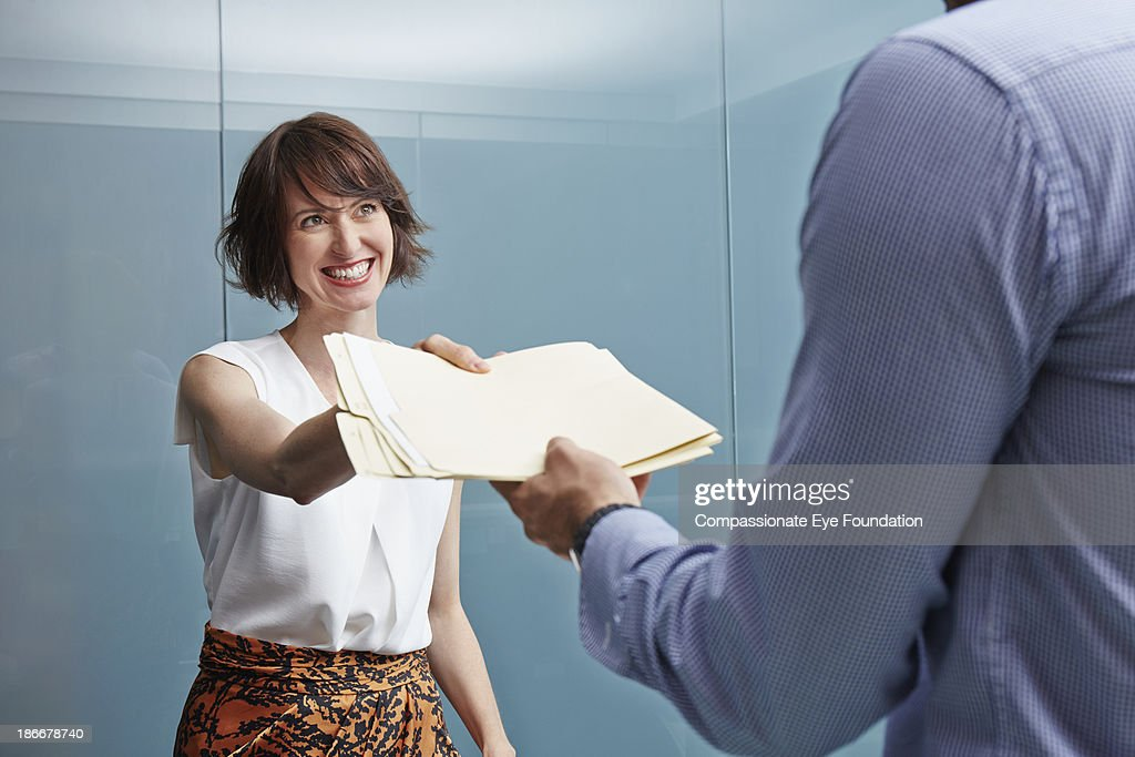 Woman handing man with documents in office