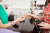 Woman handing over credit card to shop assistant
