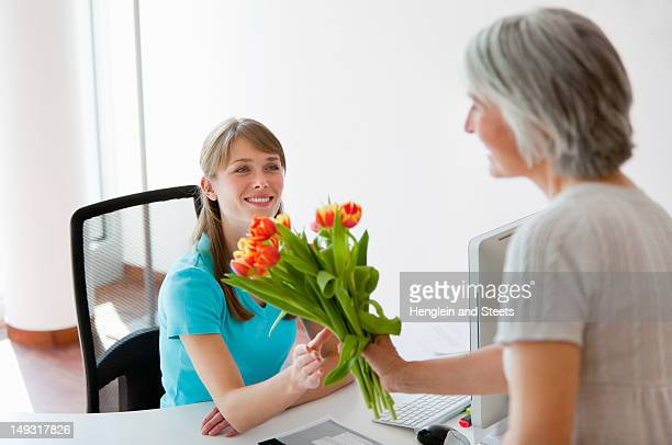 Woman handing receptionist flowers