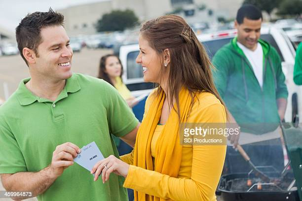 Woman Handing Tickets to Man at Tailgate Party