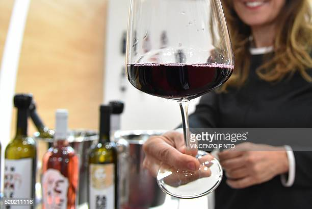A woman hands a glass of wine from the 'Le Moire' wine maker of the Italian Calabria region on April 10 2016 during the 50th edition of the Vinitaly...