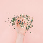 New Year or Christmas Top view of woman hands black manicure covered golden stars confetti with copy space millennial pink color paper background minimal style. Template for feminine blog social media