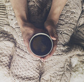 Woman hands holding tasty warm coffee espresso in ceramic cup with cookie sitting on bed with plaid. Home concept. Top View.