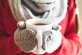 Female hands holding hot mug close up. Woman hands in woolen mittens holding a cup with hot cocoa, tea or coffee.