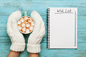 Woman hands in mittens hold cup of hot cocoa or chocolate with marshmallow and notebook with wish list on turquoise vintage table from above, christmas planning concept. Flat lay style.