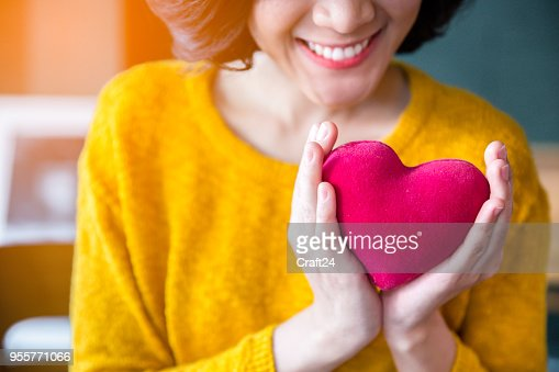 Woman  hands in yellow sweater holding pink heart. : Stock Photo