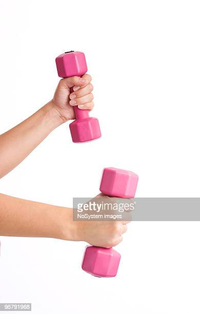 Woman hands lifting pink dumbbells