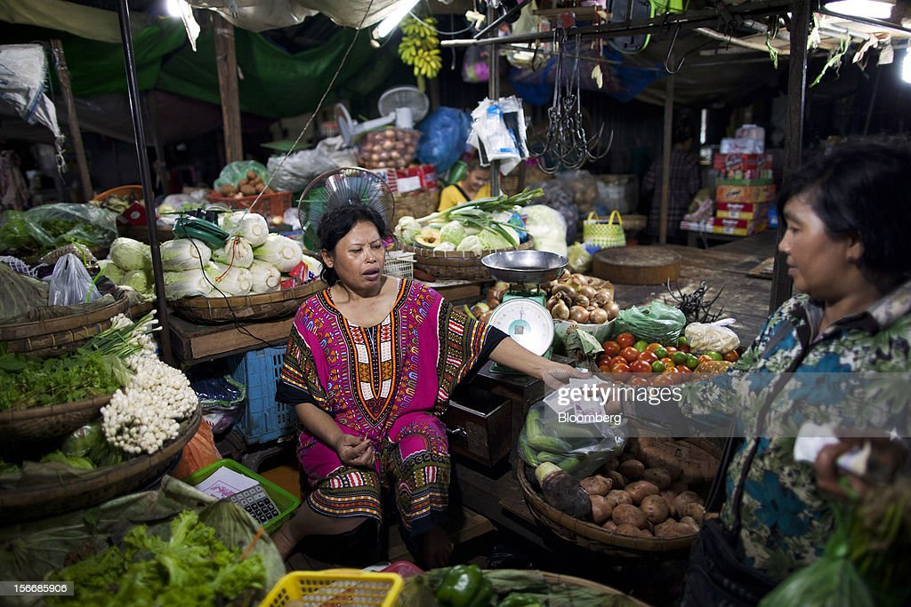 A woman hands money to a vendor for her purchases at a vegetable stall at Kandal Market in downtown Phnom Penh, Cambodia, on Saturday, Nov. 17, 2012. U.S. President Barack Obama arrives in Phnom Penh later today to join the Association of Southeast Asian Nations (Asean) East Asia Summit, which also includes leaders from Japan, South Korea, India, Russia, Australia and New Zealand. Photographer: Will Baxter/Bloomberg via Getty Images