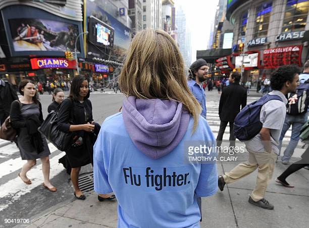 A woman hands out packages of hand sanitizing wipes at Times Square in New York on May 1 2009 to help people take precautions against the spread of...