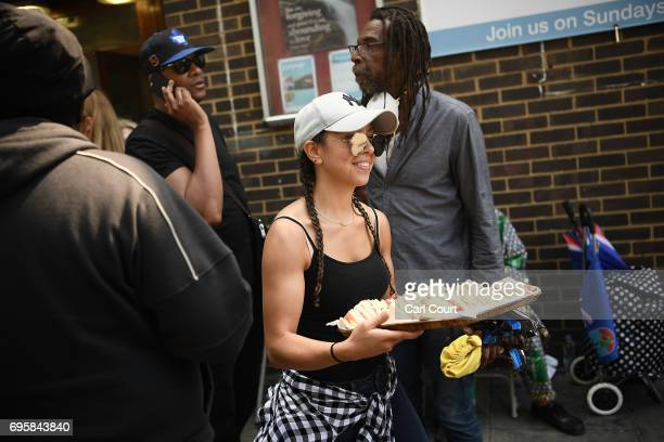 A woman hands out sandwiches near the burning 24 storey residential Grenfell Tower block in Latimer Road West London on June 14 2017 in London...