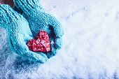 Woman hands in light teal knitted mittens are holding a beautiful a entwined vintage romantic red heart in a snow background. Love and St. Valentine concept.