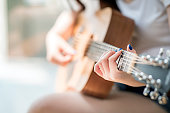 woman hands playing acoustic guitar, close up view, shallow DOF
