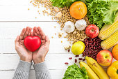Woman hands holding red heart shape ball with various kinds of colorful healthy medicinal fruits, vegetables and nuts aside on white wood table, top view