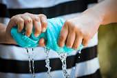 Woman hands squeeze wet blue towel and water drop