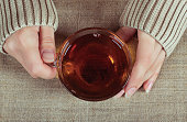 Graceful hands of a girl with a cup of tea and a long-sleeved shirt. Cozy home atmosphere. Tea time.