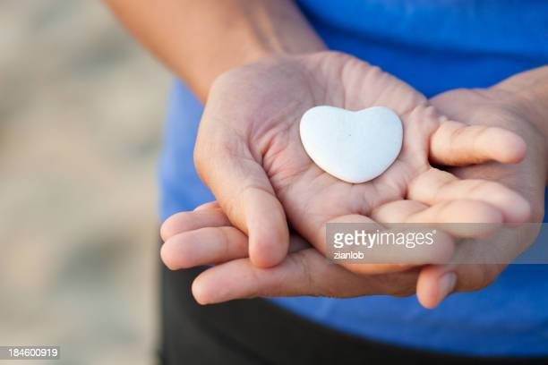 Woman hands with blue shirt showing a heart of stone.