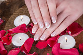 Young girl hands with french nails polish style and wooden bowl with water and floating candles and red rose petals. Manicure and Beauty concept. Close up, selective focus