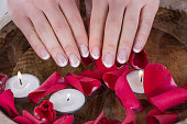 Girl hands with french nails polish style and wooden bowl with water and floating candles and red rose petals. Manicure and Beauty concept. Close up, selective focus