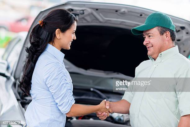 Woman handshaking with a mechanic
