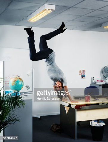 Woman handstanding at the edge of her office table