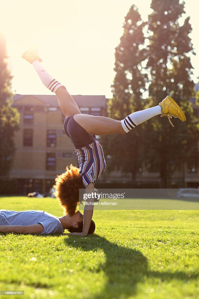 woman handstands over man in park : Stock Photo
