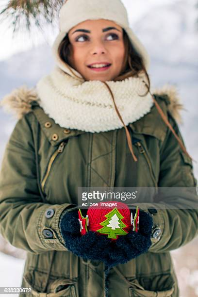 Woman hanging a colorful Christmas ornament in the snow