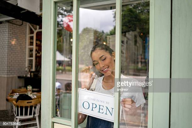Woman hanging an open sign at a restaurant