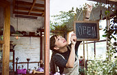 Woman hanging an open sign