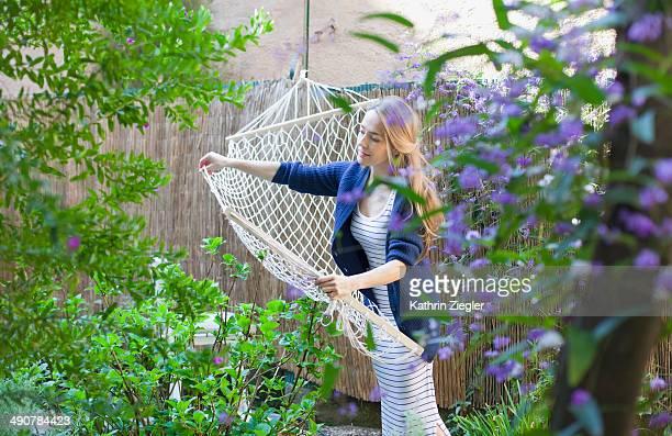 woman hanging hammock in garden