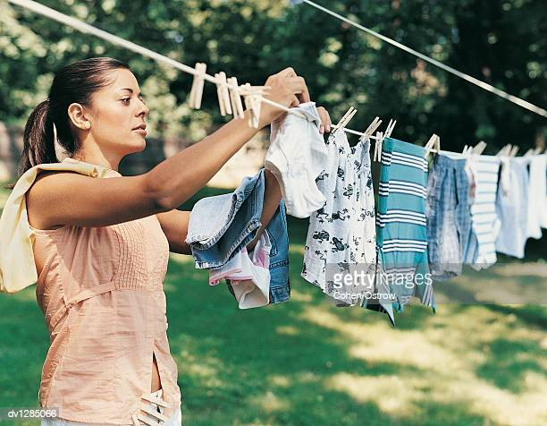 Woman Hanging Her Laundry Out to Dry on a Washing Line in Her Garden