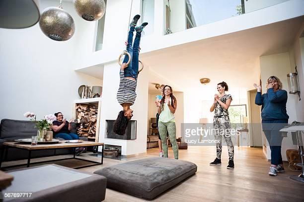 Woman hanging in the rings in a livingroom