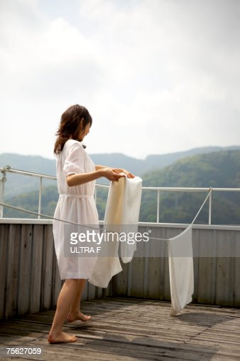 Woman hanging laundry on clothes line on wooden patio : Stock Photo