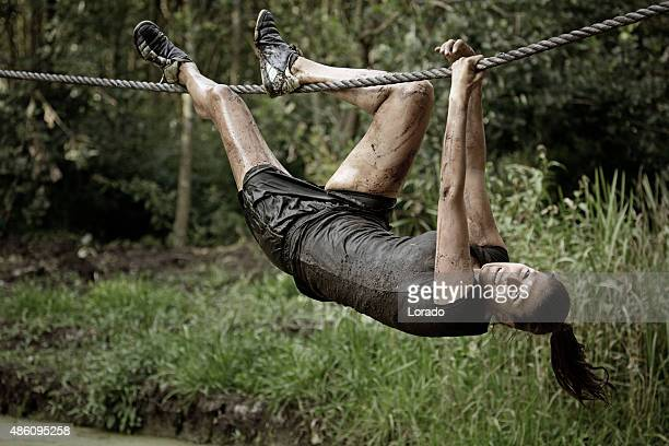 woman hanging on rope during obstacle run