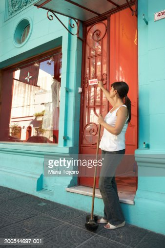 Woman hanging open sign outside shop, holding broom