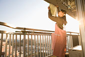 Woman hanging out laundry at balcony