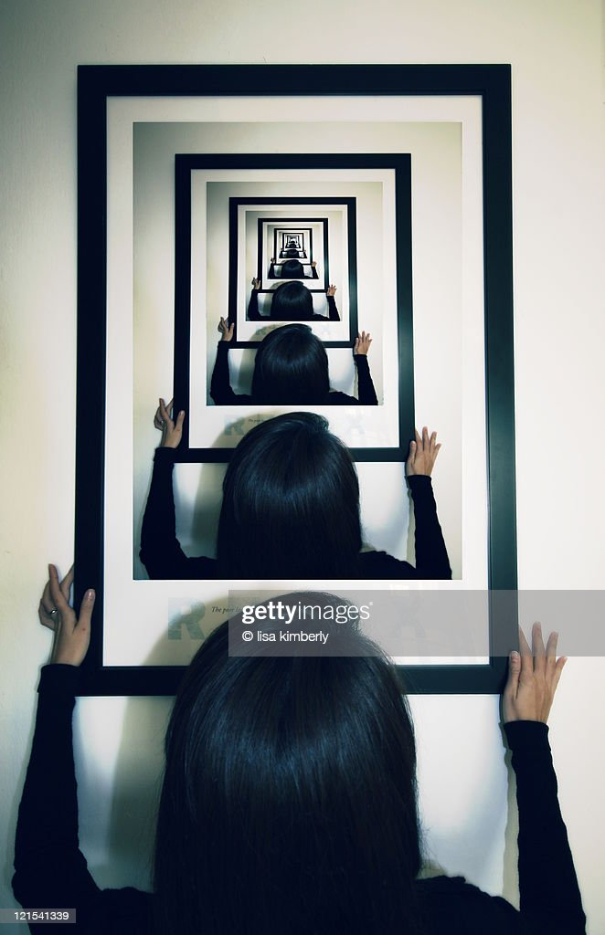 Woman hanging photo on wall with droste effect : Stock Photo