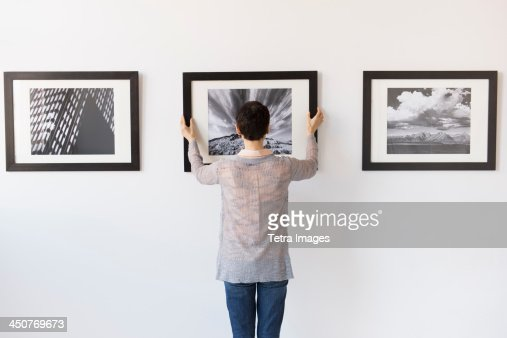 Woman hanging photographs in art gallery